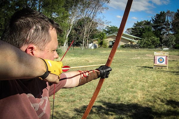 Man drawing and aiming an English Longbow