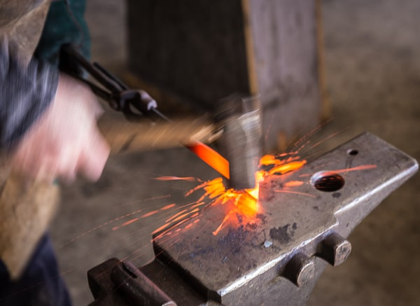 Hammer striking hot metal on an anvil sending sparks flying