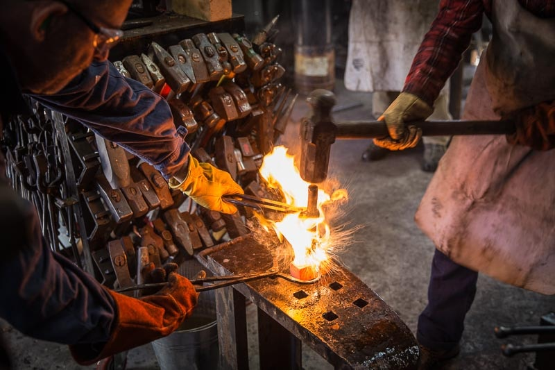 blacksmith and striker forging a hammer head